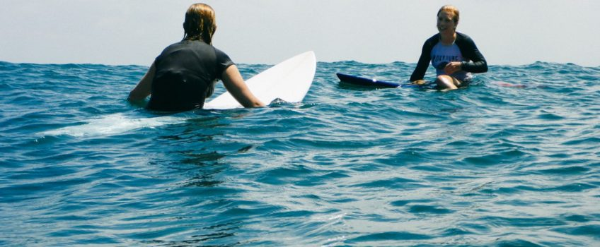 Girls surfing at Kuta Reef, Bali - Layback Travel