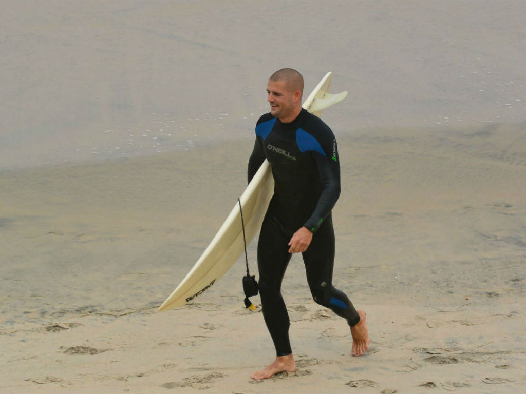 surfer coming out of water surfboard surfing beach blacks beach california layback travel surfsession