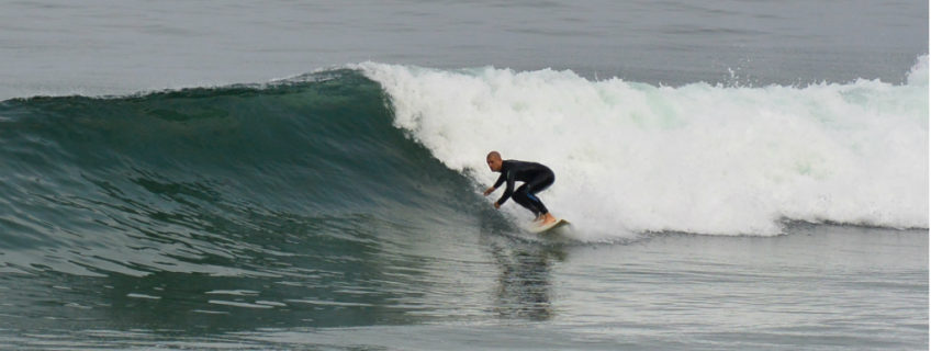 surfer on wave riding wave surfing right-hander ocean sea breaking wave surfer blacks beach california layback travel