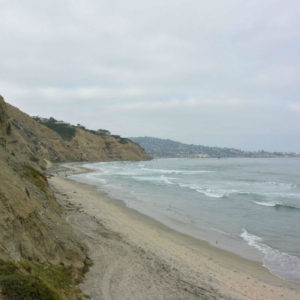 Steep cliffs surround the long beach